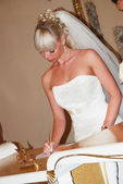 Young attractive bride signing wedding certificates — Stock Photo