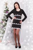 Beautiful young woman near Christmas tree — Stock Photo