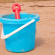 Kids blue beach bucket with red spade — Stock Photo