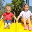 Two children playing on kids slide — Stock Photo