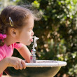 Royalty-Free Stock Photo: Girl drinking from water fountain