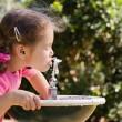flickan dricka ur fontänen — Stockfoto #12742496