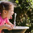 Girl child drinking at water fountain — Stok fotoğraf