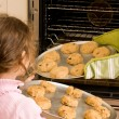 Girl helping bake cookies in oven — Stock Photo