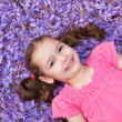 Girl child lying among purple flowers — Stock Photo