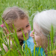 Girl laughing with Grandmother in long grass — Stock Photo