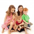 Stock Photo: Mother reading to kids on her lap