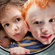 Happy kids looking through window porthole — Stock Photo