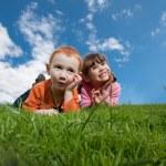 crianças engraçadas felizes, deitado na grama, com céu azul — Foto Stock