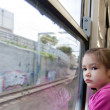 Girl looking out window of train — 图库照片
