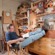 Man resting with feet up in workshop — Stock Photo #12743462
