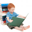 Boy leaning against books and reading — Stock Photo