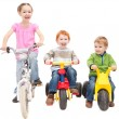 Stock Photo: Children riding bikes and kids trikes