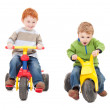 Children riding kids tricycles — Stock Photo