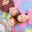 Children having fun on kids alphabet mat — Stock Photo #12743629