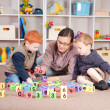 Boys playing game with kids blocks with mother - Stock Photo