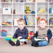 Smiling children reading kids books in play room — Stock Photo