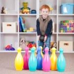 Smiling boy playing kids bowling game — Stock Photo #12743680