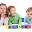 Three happy children with thankyou kids letter blocks - Stok fotoğraf