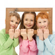 Royalty-Free Stock Photo: Three happy smiling kids looking through picture frame
