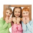Three happy smiling kids looking through picture frame — Stock Photo #12743925