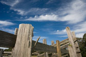 Old wooden stockyard fence with blue sky and clouds — Stock Photo