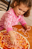 Girl child cooking homemade pizza in kitchen — Stock Photo