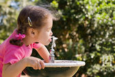 Girl drinking from water fountain — Stock Photo