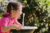 Girl child drinking at water fountain — Stock Photo