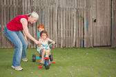 Grandmother helping kids ride trike — Zdjęcie stockowe
