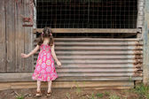 Inquisitive girl exploring old shed — Stock Photo