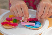 Girl making decorating cookies with icing and lollies — Стоковое фото