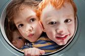Happy kids looking through window porthole — Stock Photo