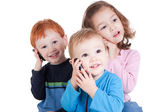 Three happy kids talking on mobile phones — Stock Photo
