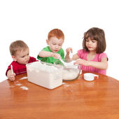 Kids measuring and mixing flour in kitchen bowl — Stock Photo