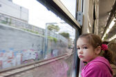Girl looking out window of train — Stok fotoğraf