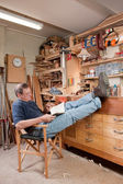 Man resting with feet up in workshop — Stock Photo