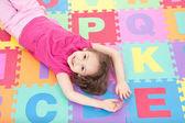 Smiling girl lying on alphabet tiles — Stock Photo