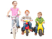 Children riding bikes and kids trikes — Stock Photo