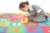 School child in uniform finishing alphabet letter puzzle — Stock Photo
