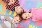 Children having fun on kids alphabet mat — Stock Photo