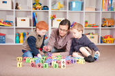 Boys playing game with kids blocks with mother — Stock Photo