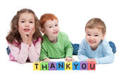 Three happy children with thankyou kids letter blocks — Stock Photo