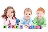 Three happy children with kids blocks — Stock Photo