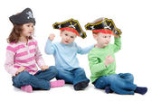 Children playing game in kids party pirate hats — Stock Photo