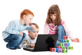 Children learning reading with kids blocks and computer — Stock Photo