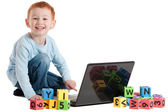 Boy child at school with computer and kids blocks — Stock Photo