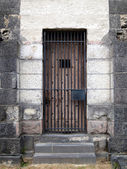Old stone jail wooden door with iron bars — 图库照片