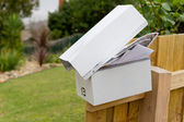 Overflowing letterbox on fence post — Stock Photo