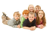 Group of happy kids laying on floor together — Stock Photo